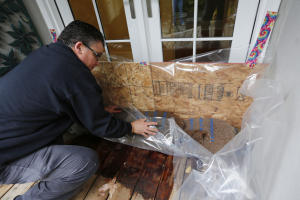 Jon Hospitalier, Palo Alto assistant director of public works, demonstrates the use of plywood, polyethylene plastic sheeting and sandbags to protect a