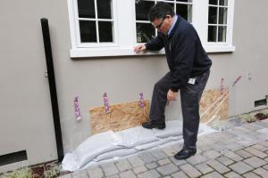 Jon Hospitalier, Palo Alto assistant director of public works, demonstrates proper sandbagging techniques using plywood, polyethylene plastic sheeting,